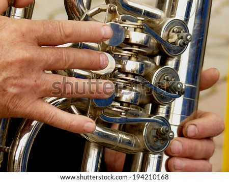 fragment of tuba with hands of musician - stock photo