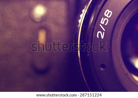 Fragment old film DSLR camera with lens. Lens and camera self-timer button. Front view. Macro. Selective focus. Vintage photo. Toning. - stock photo