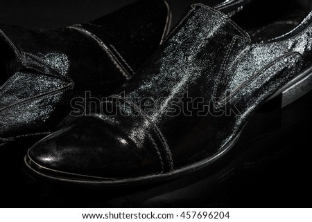 Fragmentary image of patent-leather male shoes on the luxury black background - stock photo