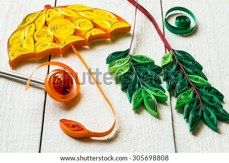 Fragments autumn decoration (umbrella, leaves mountain ash) in the technique of quilling on a white wooden background - stock photo