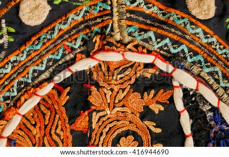 Fragments of vintage handmade blanket from India. Floral patterned embroidery on vintage backround of patchwork tradition.  - stock photo