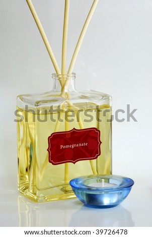 Fragrance oil with scented diffuser and a blue candle holder - stock photo