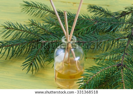 Fragrance sticks or bottle Scent diffuser with sprig fir on wooden background.   - stock photo
