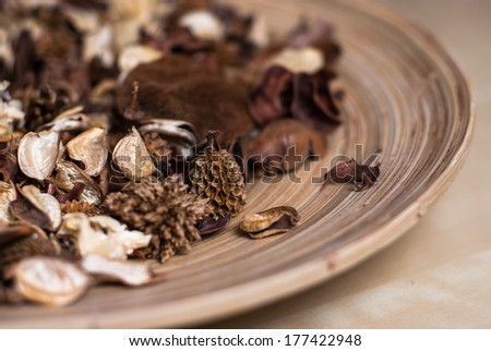 Fragrant blend of natural dried berries potpourri fruits in stylish round brown striped wooden plate on tawny brown homogeneous background