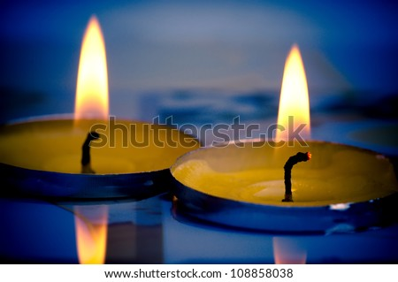 Fragrant candles with reflection in the shallow water - stock photo