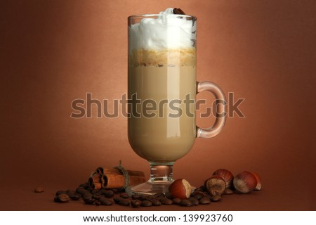 Fragrant coffee latte in glass cup with spices, on brown background - stock photo