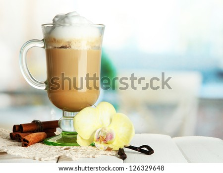 Fragrant coffee latte in glass cup with spices, on wooden table - stock photo