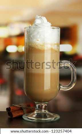 Fragrant coffee latte in glass cup with vanilla pods, on table in cafe - stock photo