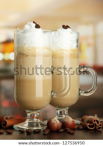 Fragrant coffee latte in glasses cups with spices, on table in cafe - stock photo
