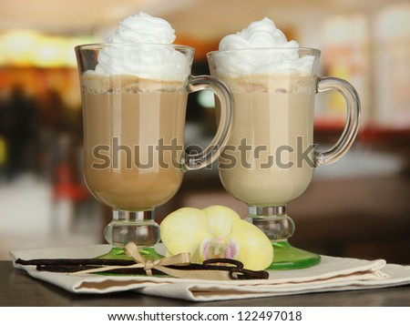 Fragrant coffee latte in glasses cups with vanilla pods, on table in cafe - stock photo