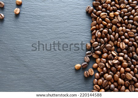 Fragrant fried coffee beans on a slate background - stock photo