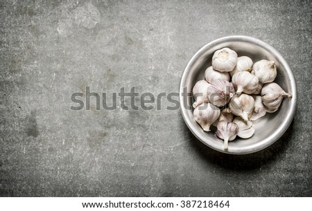 Fragrant garlic in a metal bowl. On a stone background. - stock photo