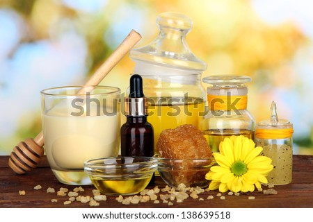 Fragrant honey spa with oils and honey on wooden table on natural background - stock photo