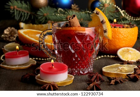 Fragrant mulled wine in glass with spices and oranges around on wooden table
