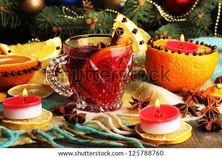 Fragrant mulled wine in glass with spices and oranges around on wooden table - stock photo