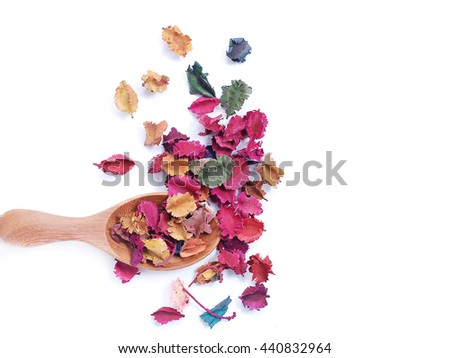 Fragrant natural potpourri with dried flowers, leaves and spices spilling out of a rectangular  wooden spoon  onto a white background for that special natural fragrance   - stock photo
