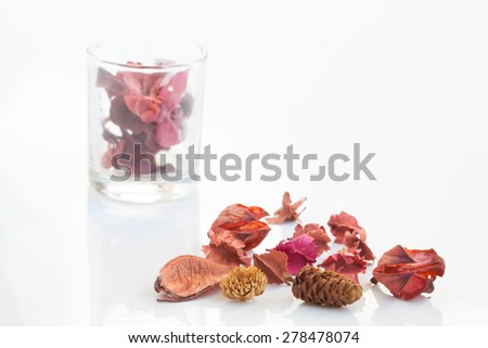 Fragrant natural potpourri with dried flowers, leaves and spices with a glass container background on white  - stock photo