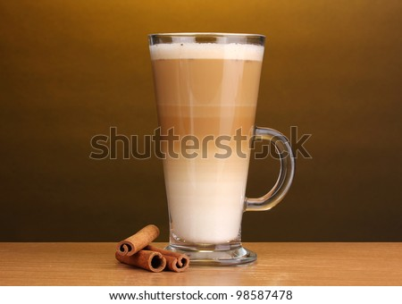 Fragrant ?offee latte in glass cup and cinnamon on wooden table on brown background - stock photo