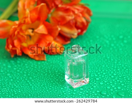 Fragrant perfume bottle on background of tulips - stock photo