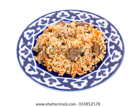 Fragrant pilaf with lamb meat and dried apricots on authentic oriental plate. Isolated on a white background. - stock photo