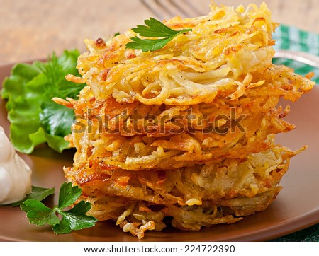 Fragrant potato pancakes with sour cream and herbs - stock photo