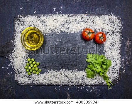frame, built of white rice with butter, pepper, parsley and cherry tomatoes place for text,frame on wooden rustic background top view - stock photo