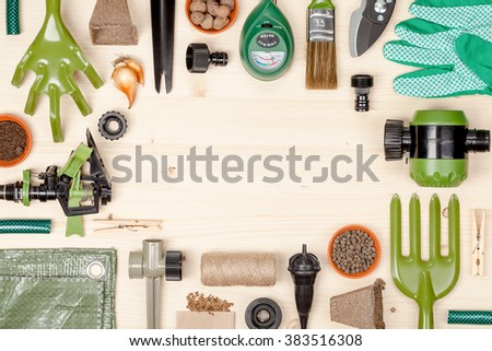frame composition with garden tools and other essentials on wooden background with copy space. gardening flat lay concept top view - stock photo