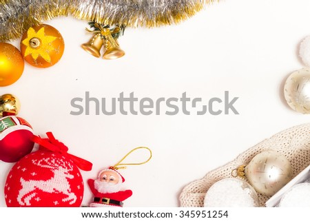 frame for text of Christmas toys on green fir branch namely big red ball with Christmas reindeer and also red ribbon, garland and bells and toy Santa Clause - stock photo