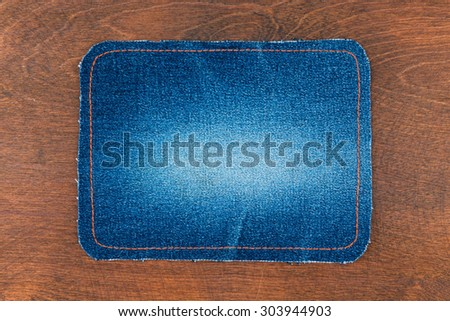 Frame for the text from a blue jeans fabric with the stitched lines of an orange thread, on a wooden background