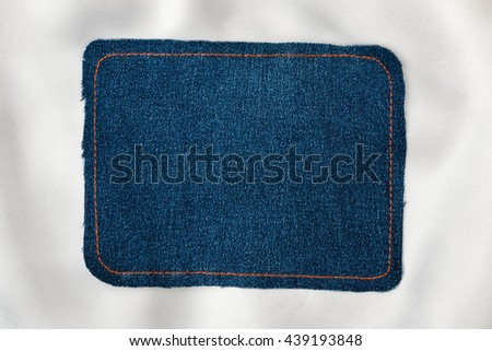 Frame for the text from a blue jeans fabric with the stitched lines of an orange thread, on a white silk