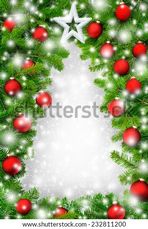 Frame made of fir branches, red baubles and snow building a border in the shape of a Christmas tree - stock photo