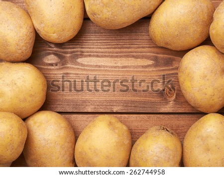 Frame made of fresh washed potatoes over the wooden table's surface as a copyspace background composition - stock photo