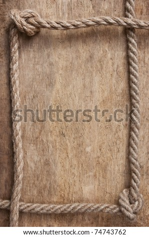 frame made of rope on a wooden background - stock photo