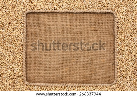 Frame made of rope with  pearl barley  grains on sackcloth, with place for your creativity - stock photo