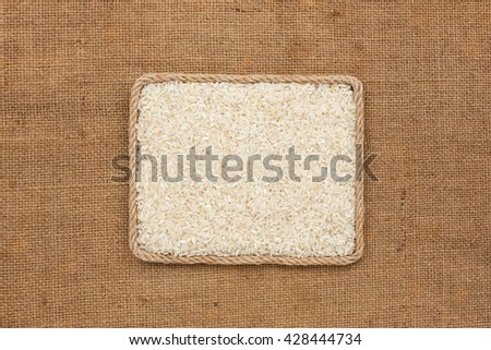 Frame made of rope with rice grains on sackcloth, view from above, with place for your text - stock photo