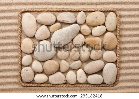 Frame made of rope with white  stones on the wavy sand - stock photo