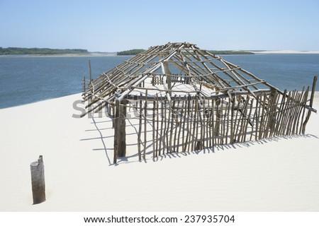 Frame of a Brazilian beach shack taken over by shifting sand dunes in Maranhão - stock photo