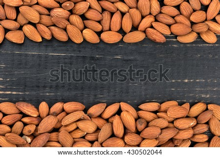 Frame of almond nuts on a blank dark wooden background