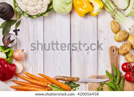 Frame of assorted healthy fresh farm vegetables, a cutting board, knife, salt and pepper mill on a white wooden background with central copy space, overhead view - stock photo