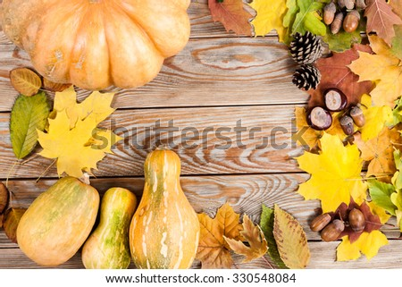 Frame of autumn leafs with pumpkins, acorn and chestnut on wooden background. - stock photo