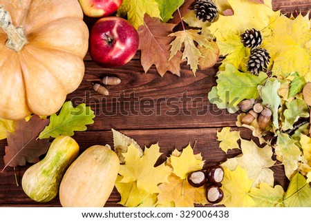 Frame of autumn leafs with pumpkins, apples, acorn and chestnut on wooden background. - stock photo