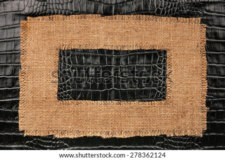Frame of burlap, lies on a background of crocodile leather, with place for your text - stock photo