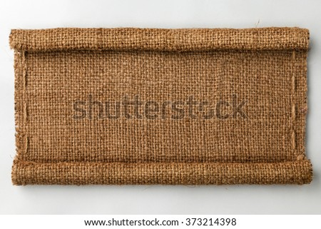 Frame of burlap with curled edges in the form of a scroll, lies on a white background, can be used as texture