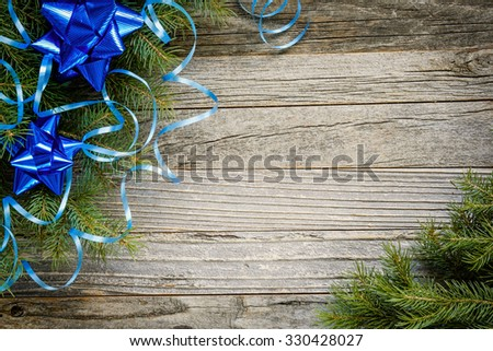 Frame of Christmas fir tree branches with blue decorations on an old wooden board, copy space for text, top view.
