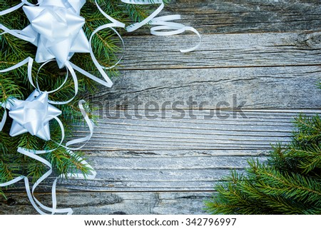 Frame of Christmas fir tree branches with white decorations on an old wooden board, copy space for text, top view.