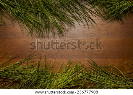 Frame of Christmas greenery on wooden background - stock photo
