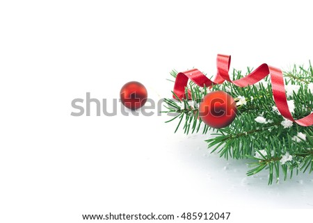 Frame of Christmas tree branches with red baubles, ribbon and snowflakes isolated on white