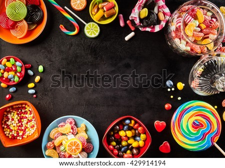 Frame of colorful bright assorted candy in bowls and jars, candy canes and rainbow colored spiral lollipops on black with scattered candy hearts and jellybeans around a central copy space on slate - stock photo