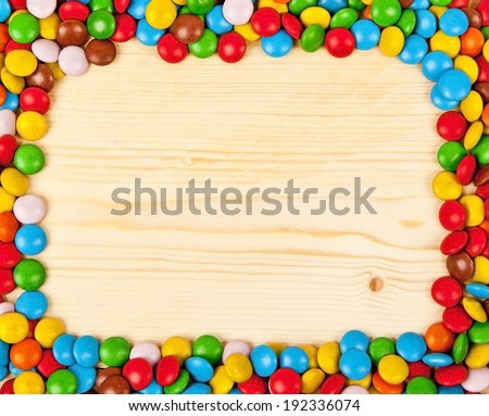 Frame of colorful candy on wood background with space for your text - stock photo