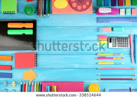 Frame of colourful stationary on blue wooden background - stock photo